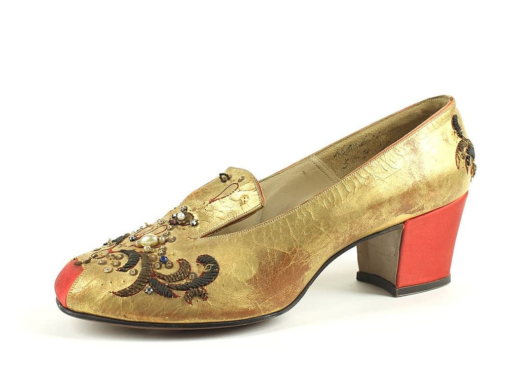 A gold shoe with a red heel from the 18th century